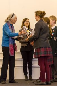 Dr Jane Goodall, DBE and Chloe Ward from National Geographic KIds Magazine giving prizes to school members; photo credit @Roger Marks Photography