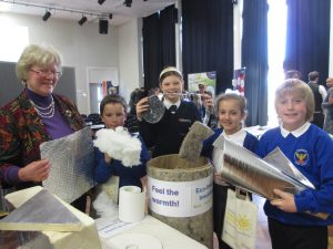 Cathy Cook, Schools Energy Project Co-ordinator who organised the conference, showing students from Wildground Junior School different types of insulation, with Year 8 Applemore College mentor Rose Davies.