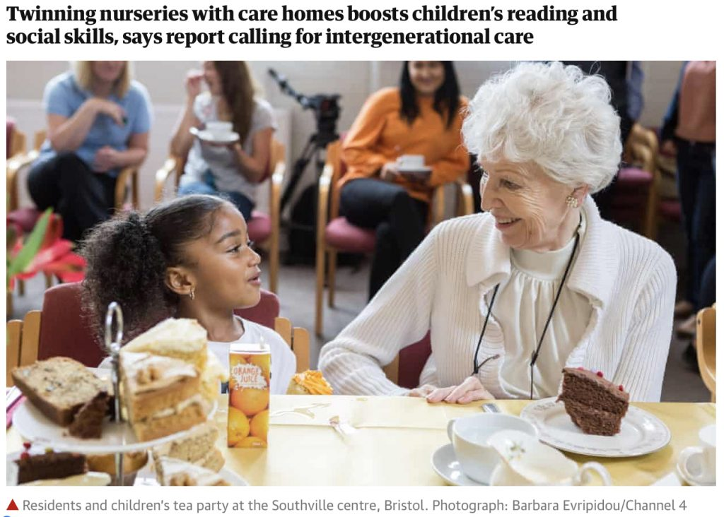 Image of an elderly lady talking to a young girl, both seated at a table enjoying tea and cake